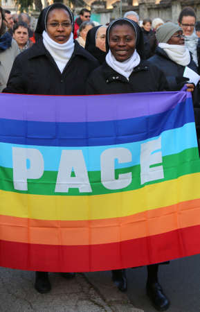 nuns: Vicenza (VI) Italy. 1st January 2016. Peace March two African nuns with flag with the word PACE peace in Italian Editorial
