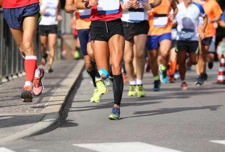 fila de personas: muchos corredores durante el maratón en la calle de la ciudad