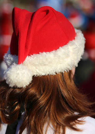 long red hair: young girl with long red hair with a red cap dressed as Santa Stock Photo