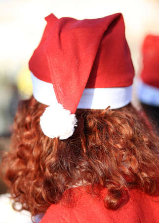 long red hair: girl with long red hair with a red cap on his head and the costume of Santa Claus Stock Photo