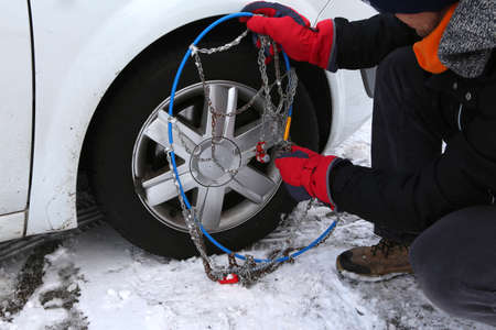mechanic assembles the snow chains in the car wheel in winter on snow Foto de archivo