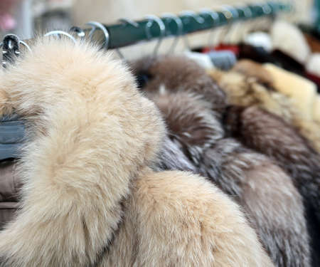 rummage: many valuable fur coat in vintage style for sale in the flea market outdoors
