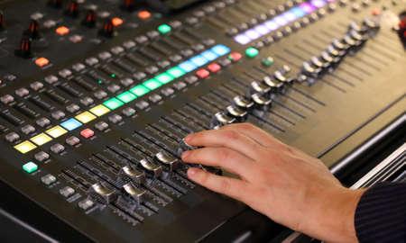 leds: La mano de un hombre en Mesa de mezclas de correo de un sistema de alta fidelidad grande con muchos potenciómetros LEDs y ecualizador de sonido durante un concierto de rock