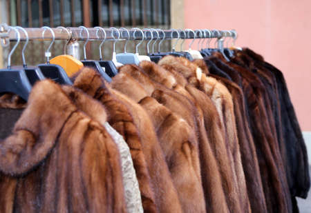 valuable: many valuable fur coat vintage style for sale in the flea market outdoors