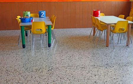 school canteen: escritorio de un jardín de infancia con frascos numerados y pequeñas sillas de color amarillo Foto de archivo