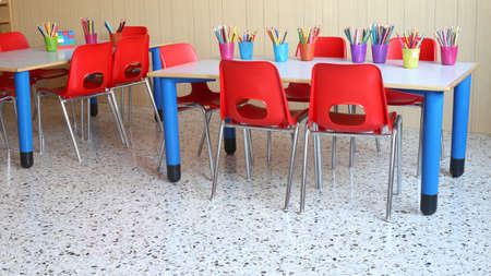 classroom of a kindergarten with red chairs and small desks and lots of colored pencils Imagens