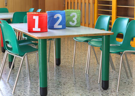 scholastic: cans with large numbers on the desk in the kindergarten