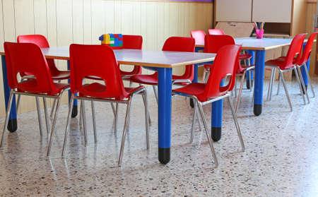 comedor escolar: aula de un jardín de infantes con sillas rojas y pequeñas mesas escolares