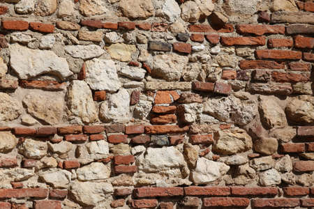 toughness: old wall of stones and red bricks with cement Stock Photo