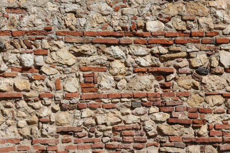 solidity: old wall of stones and red bricks with lime and cement