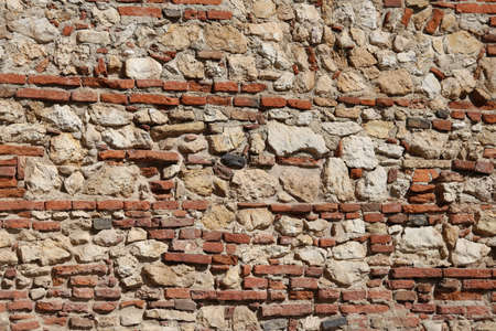 solidity: wall of stones and red bricks with lime and cement