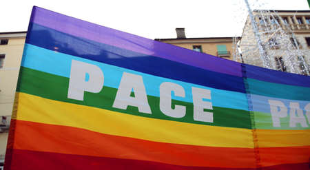activists: multi-colored peace flag during a demonstration of peace activists in an Italian city Stock Photo
