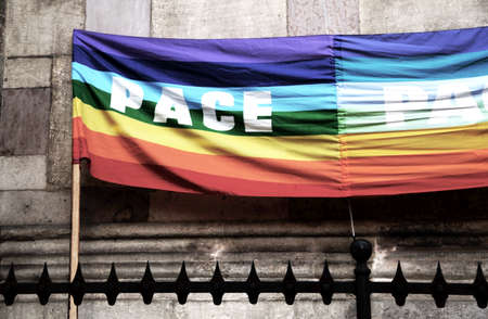 grates: dramatic rainbow peace flag during a demonstration of Italian pacifists in a square behind grates sharp