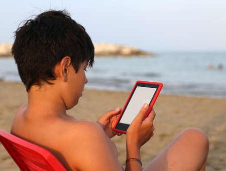 hair blacks: alone boy with hair blacks reads an ebook on the beach