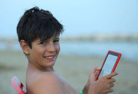 hair blacks: smiling boy with hair blacks reads an e-book on the beach to the sea in summer