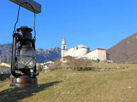 ornamentations: vintage old red lantern near the small village amid the mountains and the background of the blue sky Stock Photo