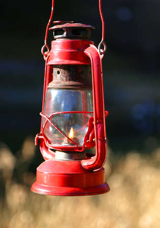 red oil lamp: vintage old red lamp oil with flame