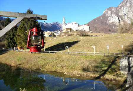 red oil lamp: vintage old red lantern near the small village amid the mountains and the background of the blue sky Stock Photo