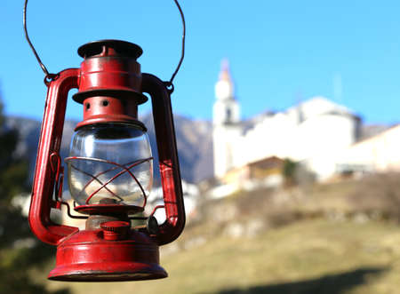 bard: vintage old red lantern near the small village amid the mountains and the background of the blue sky Stock Photo