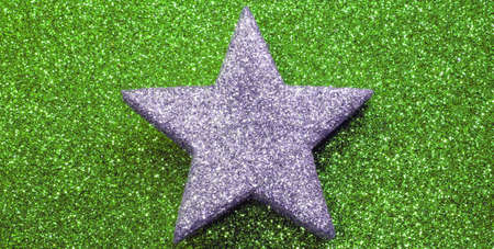 one silver star on glitter material on green shiny  background blazing bright