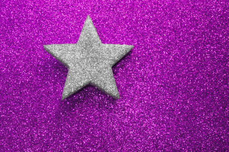 silver star: lone silver star on purple shiny background blazing bright Stock Photo