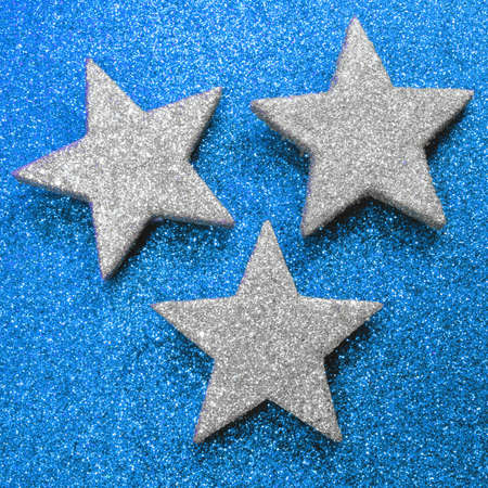 brigh: three large silver stars on bright blue illuminated background