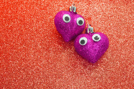 amore: two violet hearts in love with open eyes in the red background Stock Photo