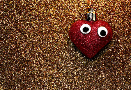 amore: lone red heart with big eyes on the dark yellow background Stock Photo