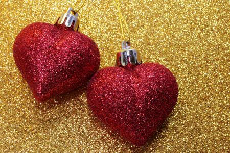 amore: two red hearts glitter on golden background shining Stock Photo