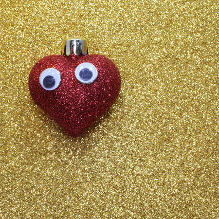 red glittery: lonely red heart with big eyes on the golden background bright shiny