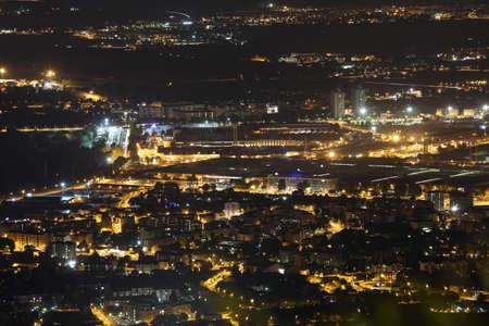 demografia: noche vista aérea de la metrópoli europea poblados con muchas luces de la ciudad Editorial