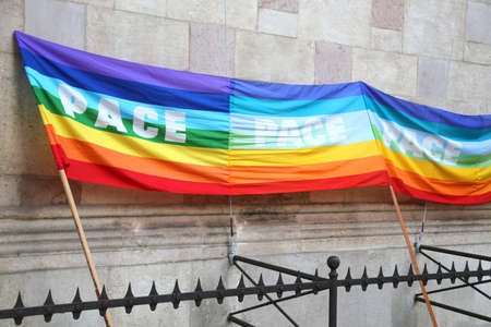 grates: multicolored rainbow peace flag during a demonstration of pacifists in an italian city behind grates Stock Photo