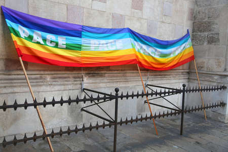 grates: multicolored rainbow peace flag during a demonstration of Italian pacifists in an italian city behind grates