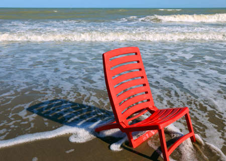 waive: little red beach chair by the sea in summer Stock Photo