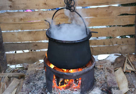 blacked: big black pot with the fire lit and the dense smoke during cooking