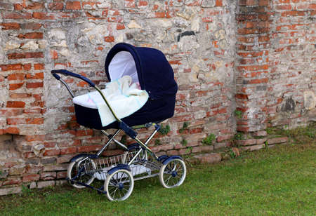 kiddy: classic pram for newborn babies on the garden and the brick wall