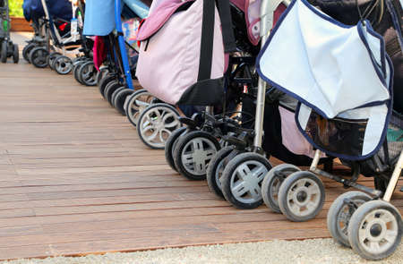 kiddy: many strollers for toddlers parked on the parquet floor of wood
