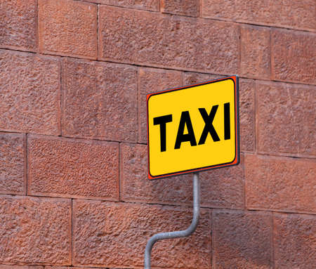 taxi sign: yellow TAXI sign on the taxi stop with a wall of an old building