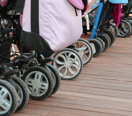 babyhood: many wheels of strollers for toddlers parked on the wooden parquet floor