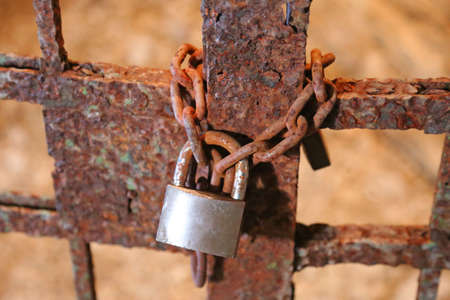 ancient prison: rusty padlock with the chain and the closed gate of old prison