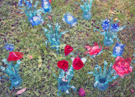 plastic made: many ecological colored flowers made from plastic bottles reciclate Stock Photo