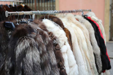 rummage: many valuable fur coat in vintage style for sale in the flea market Stock Photo