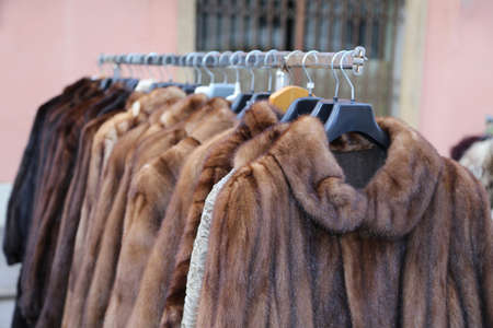 rummage: valuable fur coat in vintage style for sale in the flea market outdoors Stock Photo