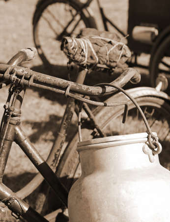 milkman: old bicycle of the last century used to transport the milk by milkman in the bin of aluminum and the bike saddle with string Stock Photo