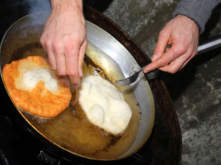 ooking: Cook hands during preparation of pancakes in hot oil