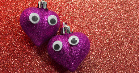 gaudy: two red hearts with eyes in the red glitter background Stock Photo