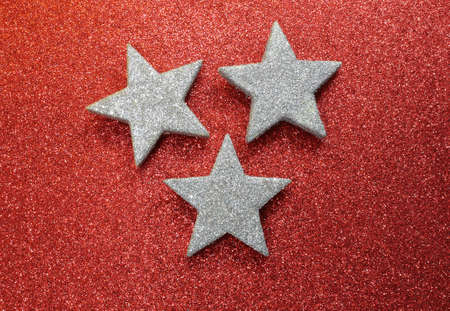 red glittery: three large silver stars on bright red glittery background illuminated
