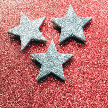 red glittery: three large silver stars on bright red glittery background Stock Photo