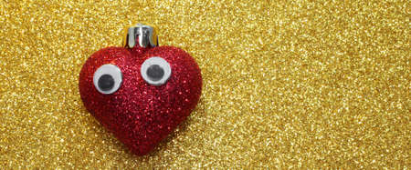 isolated lone red heart with eyes on the background bright shiny