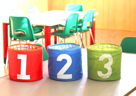 babyhood: cans with large numbers on the desk in the kindergarten